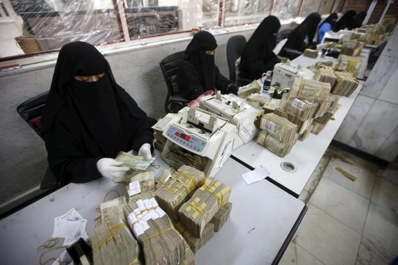 Money exchangers count stacks of Yemeni rials in of the Central Bank of Yemen in Sanaa, Yemen, November 15, 2015. REUTERS/Mohamed al-Sayaghi