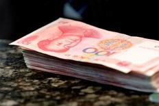 Billetes de 100 yuanes en un mostrador de un banco comercial de Pekín, China.30 de marzo 2016.Los bancos chinos extendieron nuevos préstamos por 2,03 billones de yuanes (295.740 millones de dólares) en términos netos en enero, la segunda cifra mensual más alta en los registros, pese a los esfuerzos del banco central por contener los riesgos de años de crecimiento explosivo de la deuda. REUTERS/Kim Kyung-Hoon/File Photo