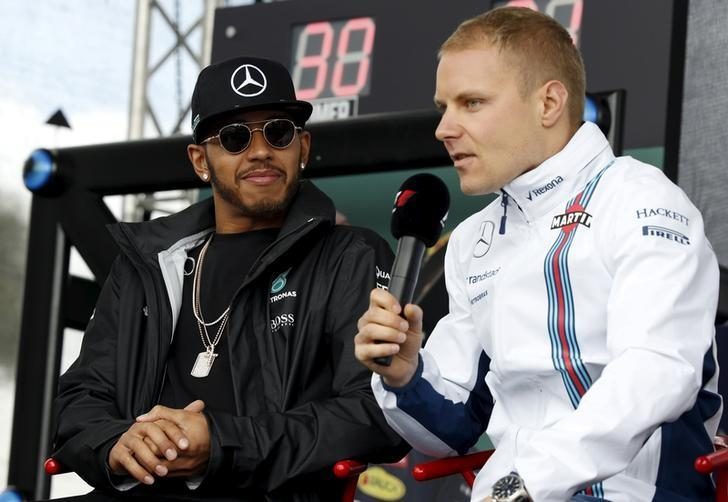 FILE PHOTO - Formula One -  Australia Grand Prix - Melbourne, Australia - 19/03/16 -  Lewis Hamilton (L) watches as Valtteri Bottas speaks to fans at the Australian Formula One Grand Prix in Melbourne.  REUTERS/Brandon Malone/File Photo