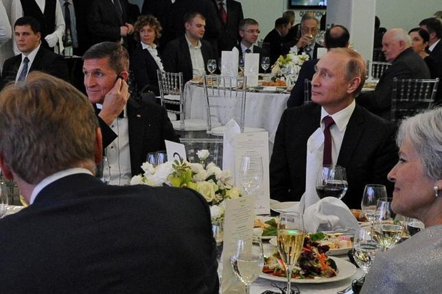 2月14日、13日に辞任したフリン前米大統領補佐官(国家安全保障担当)とロシアとの接触を巡り、トランプ大統領はフリン氏がホワイトハウスに不完全な説明をしたことを数週間前から把握していたが、その時点では辞任要求は見送った。写真は2015年12月ロシア・モスクワで行われたニュース専門局「ロシア・トゥデイ」の10周年記念イベントで、隣同士に座るフリン前米大統領補佐官(写真左)とロシア・プーチン大統領(写真右)。スプートニク提供写真(2017年 ロイター)