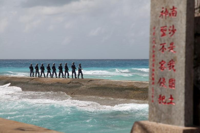 Soldiers of China's People's Liberation Army (PLA) Navy patrol near a sign in the Spratly Islands, known in China as the Nansha Islands, February 9, 2016.  REUTERS/Stringer/File Photo