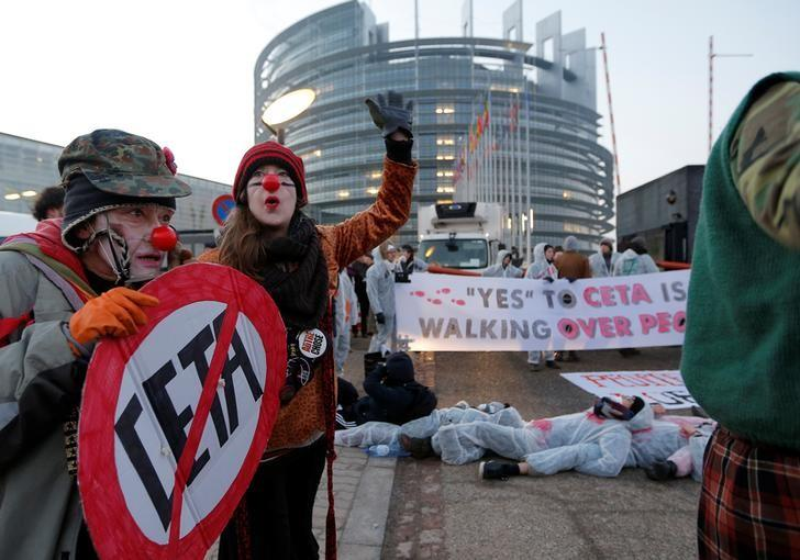 A demonstrator dressed as a clown holds a cardboard roadsign with a crossed CETA sign as he takes part in a protest against the Comprehensive Economic Trade Agreement (CETA) between the EU and Canada, in front of the European Parliament in Strasbourg, France, February 15, 2017.  REUTERS/Vincent Kessler