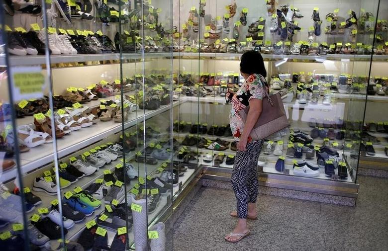 A woman stands in a shoes shop in Rome, Italy, August 11, 2016. Picture taken August 11, 2016. REUTERS/Max Rossi