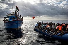Libyan fishermen throw a life jacket at a rubber boat full of migrants. Migrants are very often not given any life jackets or means of communication by their smugglersm. Mathieu Willcocks/MOAS.eu/Courtesy of World Press Photo Foundation/Handout via REUTERS