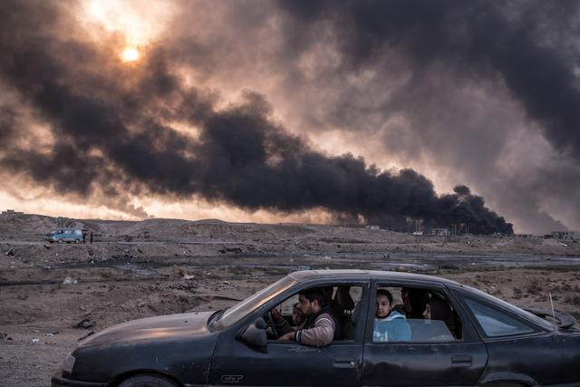 A family flees the fighting in Mosul, Iraq's second-largest city, as oil fields burned in Qayyara, Iraq, on November 12, 2016. Sergey Ponomarev for The New York Times/Courtesy of World Press Photo Foundation/Handout via REUTERS