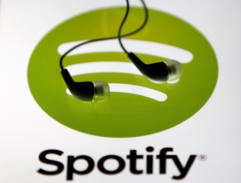 Earphones are seen on a tablet screen with a Spotify logo on it, in Zenica, Bosnia and Herzegovina, February 20, 2014. REUTERS/Dado Ruvic/File Photo