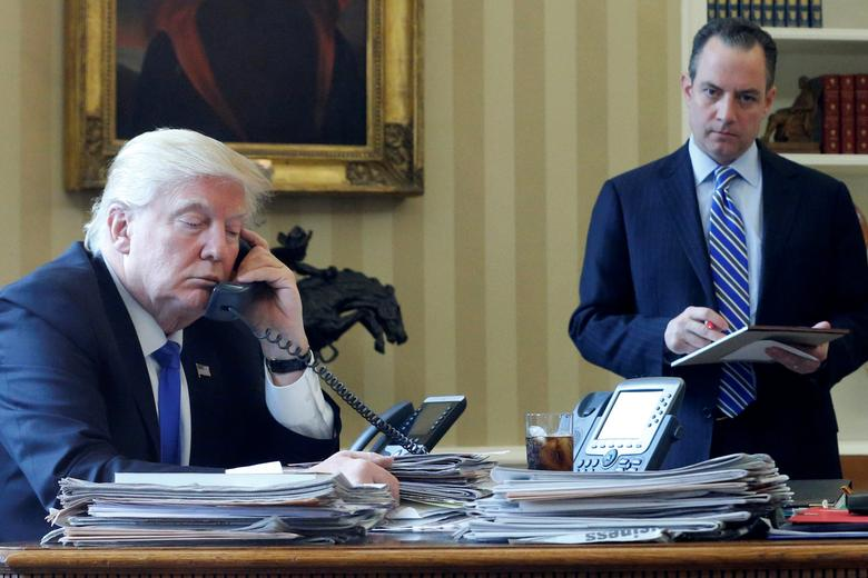 U.S. President Donald Trump, flanked by Chief of Staff Reince Priebus (R), speaks by phone with Russia's President Vladimir Putin in the Oval Office at the White House in Washington, U.S. January 28, 2017. REUTERS/Jonathan Ernst