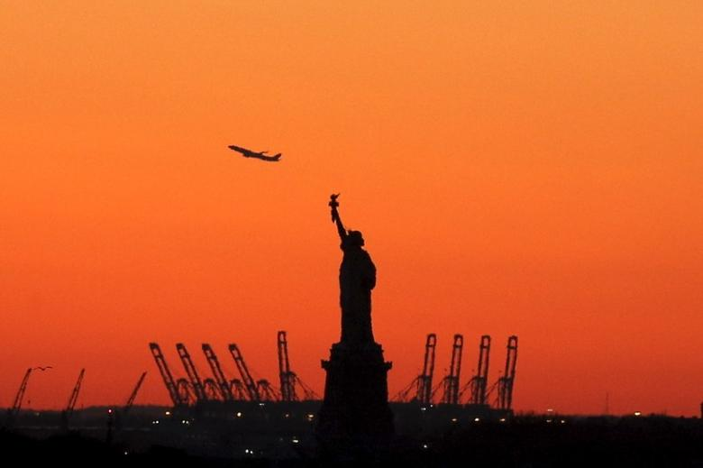 A plane is seen during take off in New Jersey behind the Statue of Liberty in New York's Harbor as seen from the Brooklyn borough of New York February 20, 2016. REUTERS/Brendan McDermid
