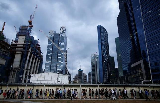 2月17日、シンガポール通産省が発表した2016年第4・四半期の国内総生産(GDP)改定値は、季節調整済みの前期比年率12.3%増、前年比2.9%増で、いずれも速報値(前期比9.1%増、前年比1.8%増)から上方改定された。製造業の急回復が寄与した。写真は夕方の通勤ラッシュアワーに、人々が駅に向かい列を成す模様。シンガポール金融街で2015年3月撮影(2017年 ロイター/Eggar Su)
