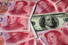 IMAGEN DE ARCHIVO. Un billete de 100 dólares rodeado de billetes de 100 yuanes, en Pekín, China. 16 de octubre 2010. El banco central de China vendió en enero la menor cantidad de divisas extranjeras en cinco meses, lo que refuerza la percepción de que la fuga de capitales ha disminuido luego de que las autoridades intensificaron su escrutinio sobre las salidas de fondos, a medida que el yuan se estabilizaba. REUTERS/Petar Kujundzic/File Photo
