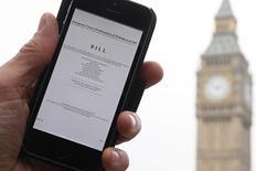 Un uomo mostra sullo smartphone la copia dell'Articolo 50  che dev'essere invocato per l'uscita dall'Ue, sullo sfondo il Big Ben, a Londra. REUTERS/Toby Melville