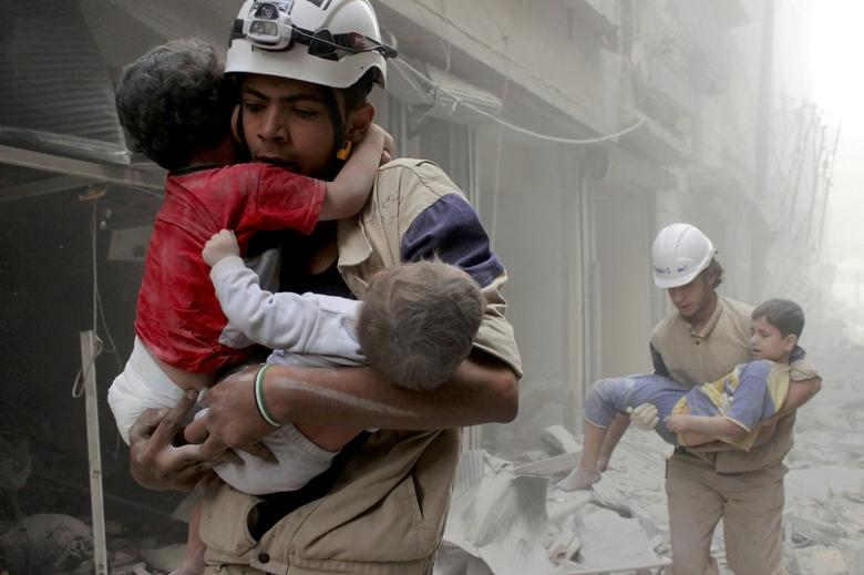 FILE PHOTO - Members of the Civil Defence rescue children after what activists said was an air strike by forces loyal to Syria's President Bashar al-Assad in al-Shaar neighbourhood of Aleppo, Syria June 2, 2014. REUTERS/Sultan Kitaz