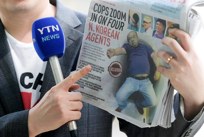 A reporter holds up a local newspaper during his report in front of the morgue at Kuala Lumpur General Hospital where Kim Jong Nam's body is held for autopsy in Malaysia February 18, 2017. REUTERS/Athit Perawongmetha