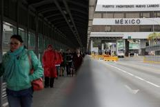 People walk near the international border port in Nuevo Laredo, Mexico, January 28, 2017. REUTERS/Daniel Becerril