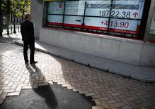 Un hombre mira un tablero electrónico que muestra el promedio Nikkei de Japón fuera de una correduría en Tokio, 1 de diciembre 2016.El índice Nikkei de la bolsa de Tokio anotó leves ganancias el lunes en medio de un débil volumen de negocios, luego de que los inversores se abstuvieron de participar en una sesión donde los mercados de Estados Unidos estarán cerrados por un feriado. REUTERS/Kim Kyung-Hoon