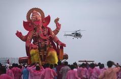 Вертолет береговой охраны Индии пролетает над религиозной процессией, несущей статую Ганеши к Аравийскому морю во время праздника Ганеша-чатуртхи в Мумбаи. 18 сентября 2013 года. Россия отправит первую партию из 200 военных вертолетов в Индию в 2019 году, часть из них будет собрана на территории южноазиатской страны, сказал глава российской госкомпании Вертолеты России в понедельник. REUTERS/Danish Siddiqui