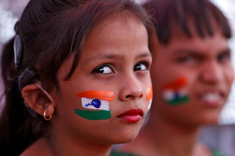 Children with the colours of the Indian national flag painted on their faces wait to perform during the Republic Day parade in Ahmedabad, India January 26, 2017. REUTERS/Amit Dave/Files