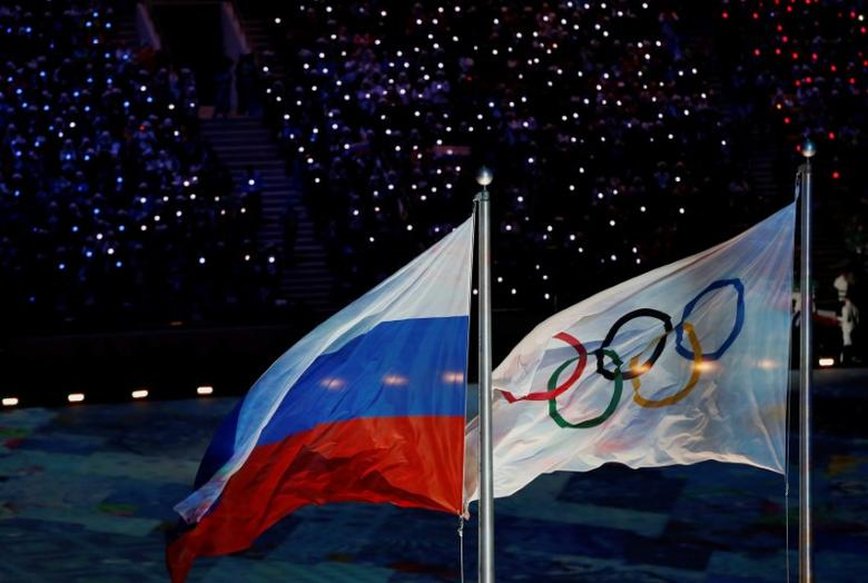 The Russian national flag flutters next to the Olympics flag during the closing ceremony for the 2014 Sochi Winter Olympics, February 23, 2014.   REUTERS/Issei Kato/File Photo