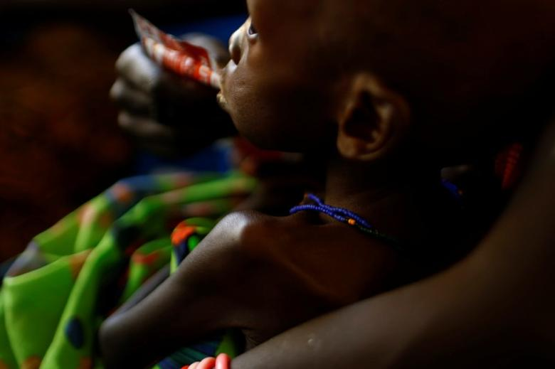 A mother feeds her child with a peanut-based paste for treatment of severe acute
