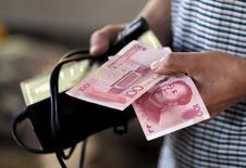 Un cliente sostiene un billete de 100 yuanes en un mercado de Pekín, China.12 de agosto 2015.Las acciones chinas extendieron sus ganancias el martes para cerrar en un máximo en casi tres meses, luego de que las expectativas de unos grandes flujos desde los fondos de pensiones hacia los mercados de valores continuaron mejorando el apetito por el riesgo. REUTERS/Jason Lee