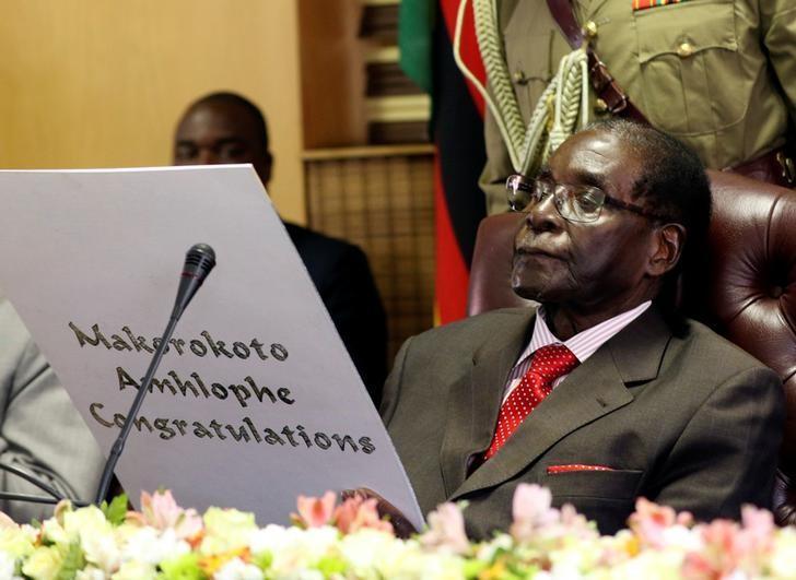 Zimbabwe's President Robert Mugabe reads a card during his 93rd birthday celebrations in Harare, Zimbabwe, February 21, 2017. REUTERS/Philimon Bulawayo