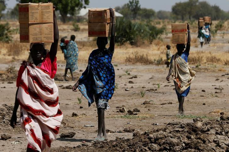 Women carry boxes of nutritional food delivered by the United Nations World Food Programme (UN WFP), in Rubkuai village, Unity State, South Sudan February 16, 2017. REUTERS/Siegfried Modola