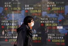 En la imagen, un hombra pasa ante un letrero electrónico que muestra la cotización del Nikkei, el Dow Jones y otros índices en una casa de valores de Tokio, el 26 de enero de 2017.El índice Nikkei de la bolsa de Tokio registró escasa variación el miércoles, incapaz de extender una racha de ganancias de dos días luego de que el retroceso del yen frente al dólar se detuvo. REUTERS/Kim Kyung-Hoon