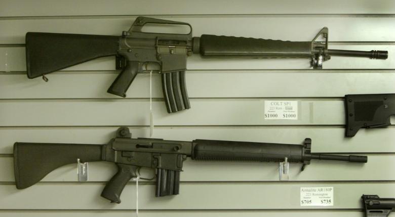 Assault-style rifles hang on display inside a Dallas, Texas gun shop, September 13, 2004. REUTERS/Jeff Mitchell  JM