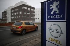 A Peugeot car drives past the logos of French car maker Peugeot and German car maker Opel at a dealership in Villepinte, near Paris, France, February 20, 2017.   REUTERS/Christian Hartmann