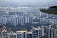 FILE PHOTO -  People look out from the observation tower of the Marina Bay Sands amongst public and private residential apartment buildings in Singapore, February 22, 2016. REUTERS/Edgar Su/File Photo