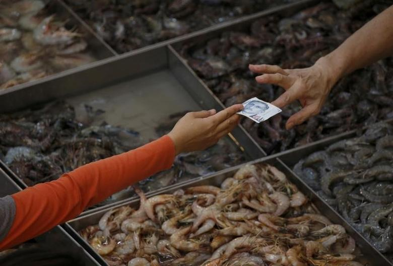 A customer pays for shrimp at a wet market in Singapore March 23, 2016. REUTERS/Edgar Su/File Photo