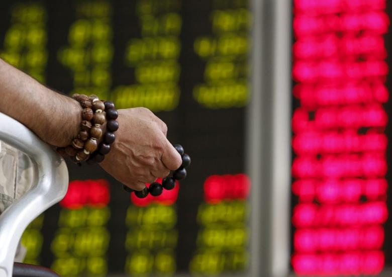 An investor holds onto prayer beads as he watches a board showing stock prices at a brokerage office in Beijing, China, July 6, 2015. China's key stock indexes showed signs of stabilizing on Monday, rising close to 3 percent, in response to unprecedented rescue measures announced over the weekend.    REUTERS/Kim Kyung-Hoon