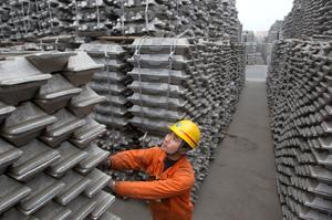 An employee checks aluminium ingots for export at the Qingdao Port