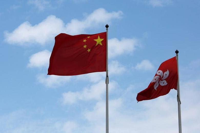 A Chinese national flag and a Hong Kong flag fly outside the Legislative Council in Hong Kong, China November 7, 2016, as China's parliament passed an interpretation of Hong Kong's Basic Law on Monday that says lawmakers must swear allegiance to the city as part of China.  REUTERS/Bobby Yip/File Photo