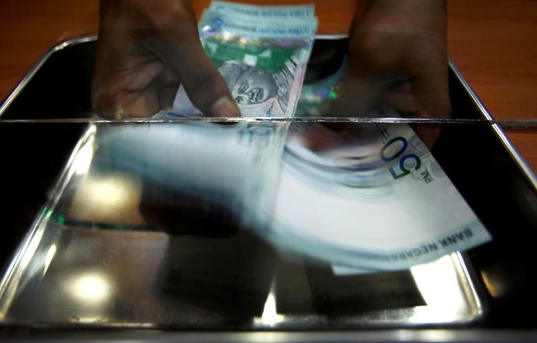 FILE PHOTO - A money changer counts ringgit at a shop in Putrajaya, outside Kuala Lumpur, October 26, 2007. REUTERS/Bazuki Muhammad/File Photo