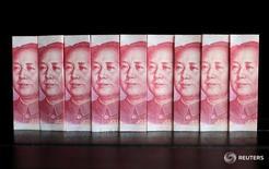 """Купюры китайской валюты юань в Пекине 11 июля 2013 года. Регулятор валютного рынка КНР сообщил в понедельник, что намерен разрешить иностранным инвесторам на межбанковском рынке заниматься форвардными сделками, сделками """"валютный своп"""" и опционами. REUTERS/Jason Lee/File Photo"""