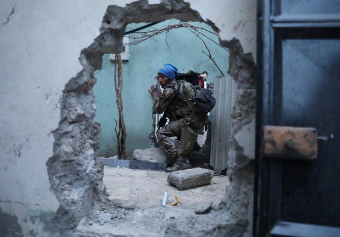 An Iraqi Special Forces soldier moves through a hole as he searches for Islamic State fighters in Mosul, Iraq February 27, 2017 REUTERS/Goran Tomasevic