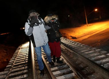 Refugees walk along railway tracks from the United States to enter Canada