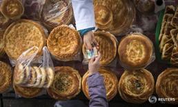 Покупатель платит за хлеб на рынке в Алма-Ате 23 января 2015 года. Инфляция в Казахстане в феврале в месячном выражении ускорилась до 1,0 процента с 0,8 процента в январе 2017 года, сообщил комитет по статистике Минэкономики в среду. REUTERS/Shamil Zhumatov