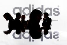 FILE PHOTO: Shareholders of Adidas Group silhouetted in front of the company logo in Fuerth near Nuremberg, Germany, May 8, 2008.  REUTERS/Michaela Rehle/File Photo