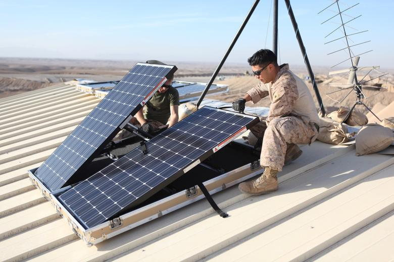 FILE PHOTO: U.S. Marine Corps Corporal Robert G. Sutton (L) and Corporal Moses E. Perez, field wireman with Combat Logistics Regiment 15 install new solar panels on Combat Outpost Shukvani, Helmand province, Afghanistan, November 19, 2012.   U.S. Marine Corps/Lance Cpl. Alexander Quiles/Handout/File Photo via REUTERS