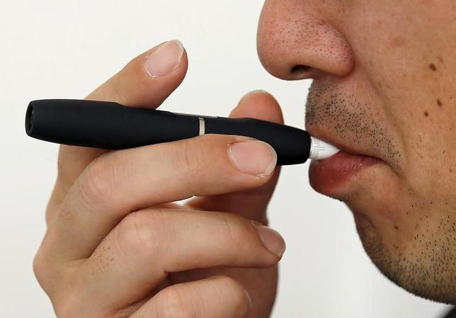 3月2日、フィリップ・モリス・インターナショナル(PMI)は、品薄が続いている加熱式新型たばこ「iQOS(アイコス)」のデバイスについて、今年半ばにはフル供給できる体制になるとの見通しを示した。写真は「アイコス」を試す顧客。都内の販売店で昨年3月撮影(2017年 ロイター/Toru Hanai)