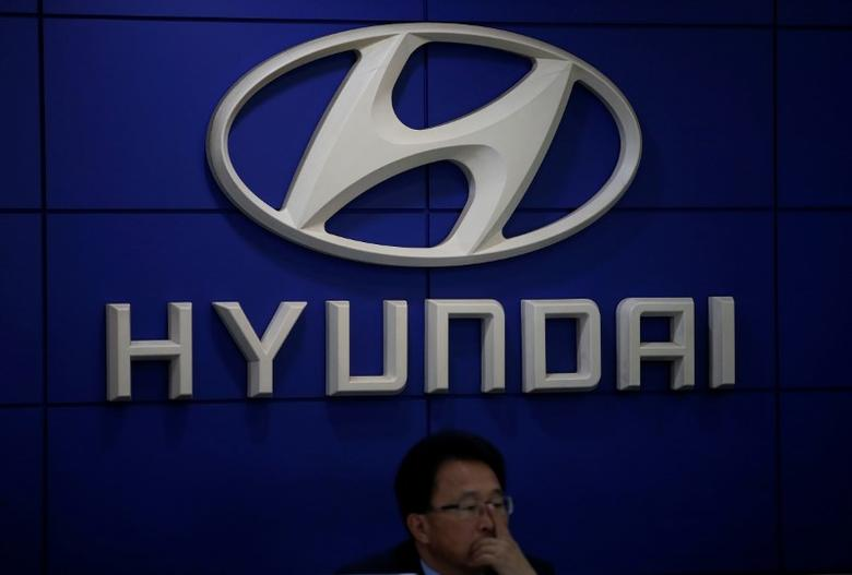 An employee sits in front of the logo of Hyundai Motor at its dealership in Seoul, South Korea October 26, 2016.  REUTERS/Kim Hong-Ji
