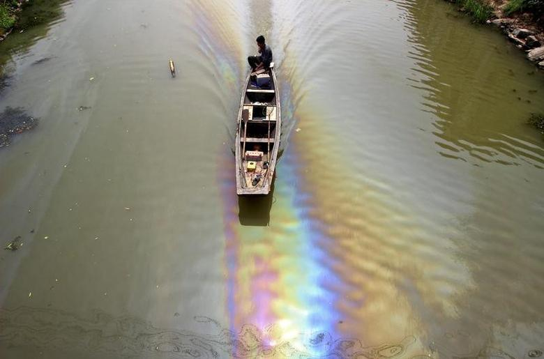 A man drives a boat along a river polluted by leaked fuel, in Shaoxing, Zhejiang province, China, April 29, 2015. REUTERS/Stringer