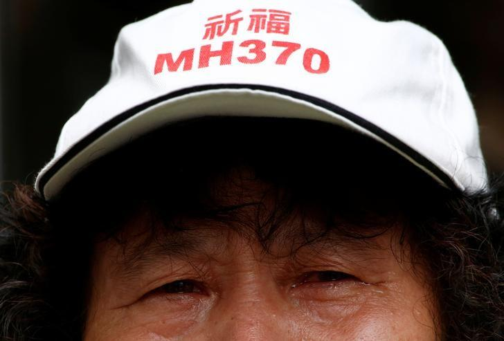 A family member of a passenger aboard Malaysia Airlines flight MH370 which went missing in 2014 reacts during a protest outside the Chinese foreign ministry in Beijing, July 29, 2016. The hat reads ''Pray for MH370'' REUTERS/Thomas Peter