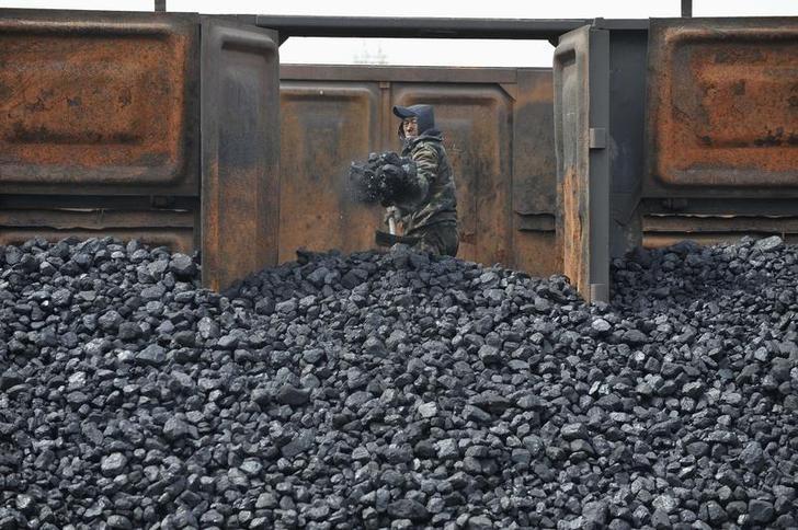 2010年4月资料图,沈阳一座铁路车站的煤场内,一名工人在从火车车厢里卸煤。REUTERS/Sheng Li