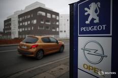 En la imagen, un modelo de Peugeot pasa junto a los logos del fabricante francés y el de Opel en un concesionario de Villepinte, cerca de París, el 20 de febrero de 2017. PSA Group ha acordado la compra de Opel al grupo estadounidense General Motors en una operación valorada en 2.200 millones de euros ($2.300 millones) que creará un nuevo gigante regional que desafiará al líder del mercado Volkswagen. REUTERS/Christian Hartmann