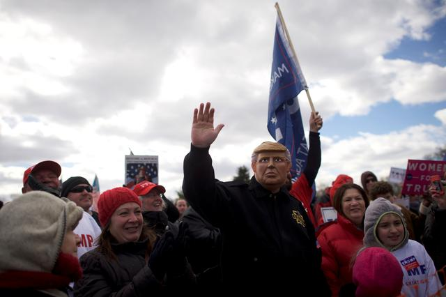 Alex Carlin waves while wearing a mask depicting President Trump during a ''People 4 Trump'' rally at Neshaminy State Park in Bensalem, Pennsylvania. REUTERS/Mark Makela