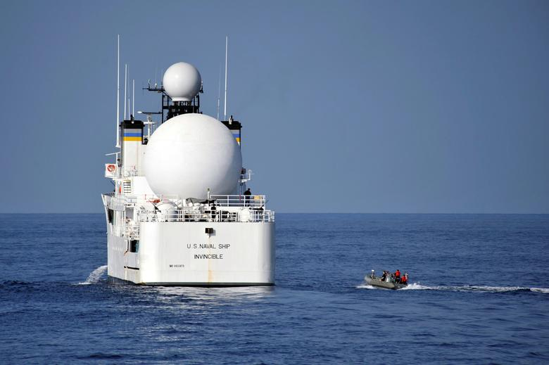 U.S. sailors in a rigid-hull inflatable boat approach the Military Sealift Command missile range instrumentation ship USNS Invincible (L) to conduct a personnel transfer in Arabian Sea on November 21, 2012.  Courtesy Deven B. King/U.S. Navy/Handout via REUTERS