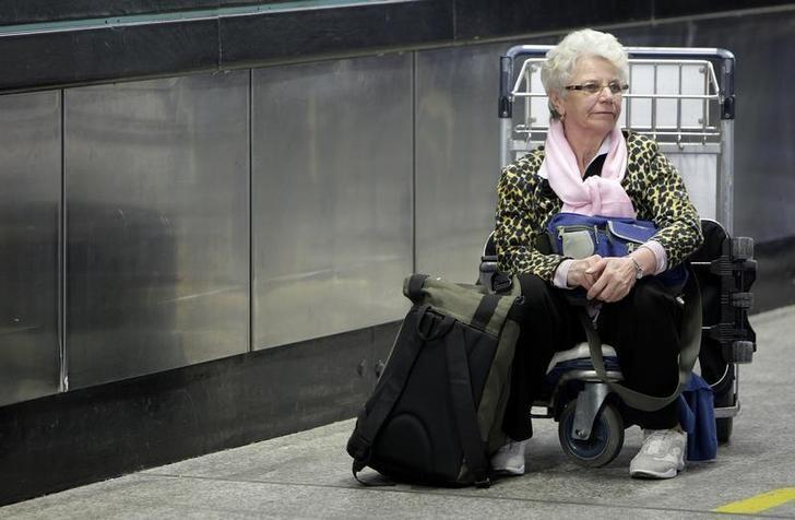 A passenger waits with her luggage at Fiumicino airport in Rome March 30, 2008.       REUTERS/Max Rossi